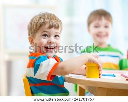 smiling kids painting at home or day care center