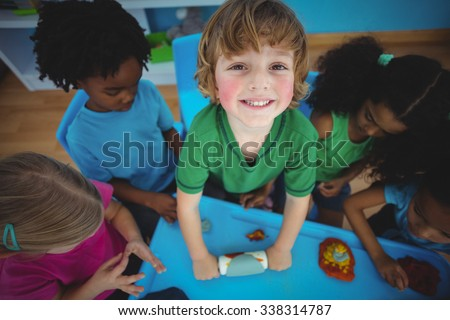 Smiling kids playing with modelling clay at their desk