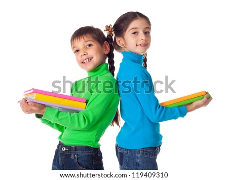 Smiling kids standing with colorful stack of books in hands, isolated on white - stock photo