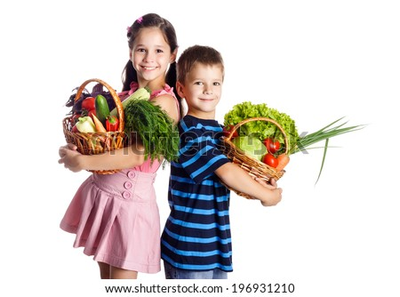 Smiling kids standing with vegetables in basket, isolated on white - stock photo