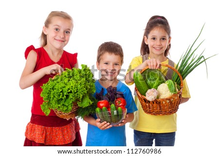 Smiling kids with fresh vegetables in basket, isolated on white