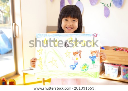 smiling Kindergarten girls holding a picture