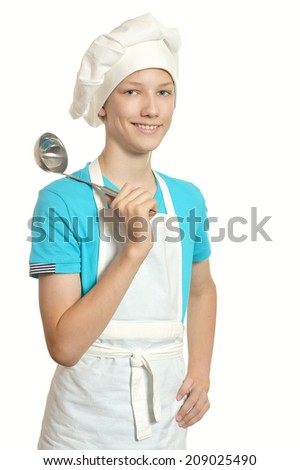 Smiling kitchen boy looking at camera holding ladle