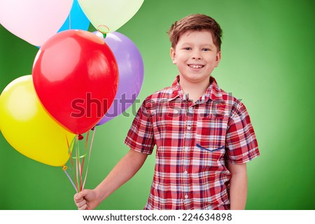 Smiling lad with balloons looking at camera in isolation - stock photo