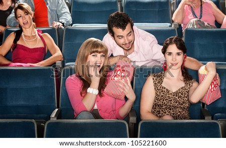 Smiling ladies sharing popcorn with man in theater - stock photo