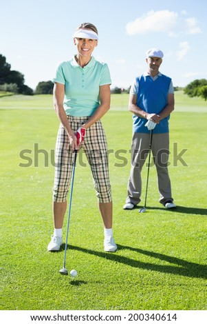 Smiling lady golfer teeing off for the day watched by partner on a sunny day at the golf course - stock photo
