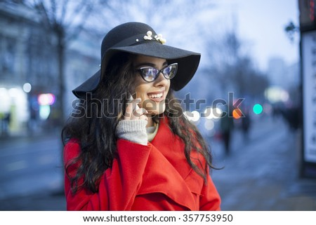 Smiling Lady in Red Coat and black hat and glasses, hold smartphone, Woman in red coat with smartphone in hands going through the city and looking shop windows. Urban Space, noise on image - stock photo