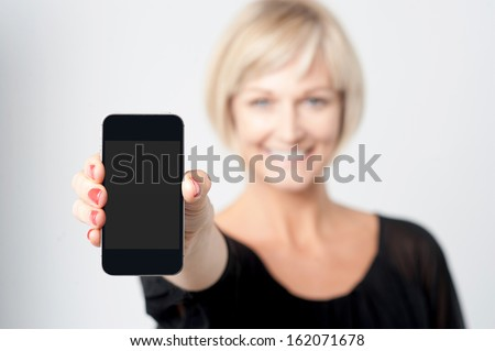 Smiling lady showcasing new mobile handset - stock photo