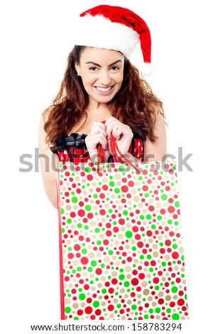 Smiling lady wearing santa cap and holding bag - stock photo