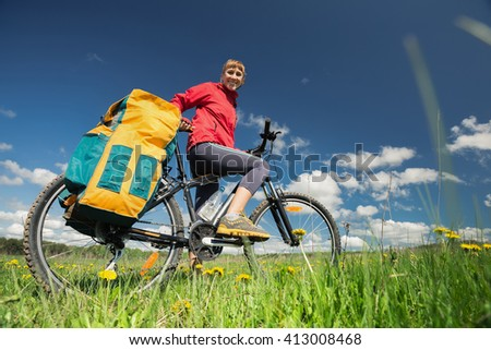 Smiling lady with loaded bicycle standing on a green meadow with flowers - stock photo
