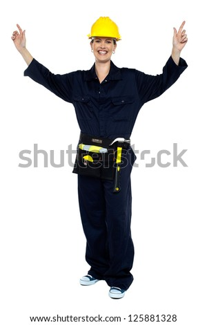 Smiling lady worker in jumpsuit raising her hands in jubilation. All on white background. - stock photo