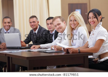 Smiling latin business woman with her business team looking at camera