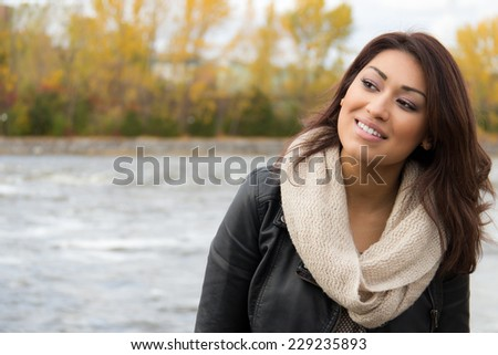Smiling Latino woman posing outdoors during fall