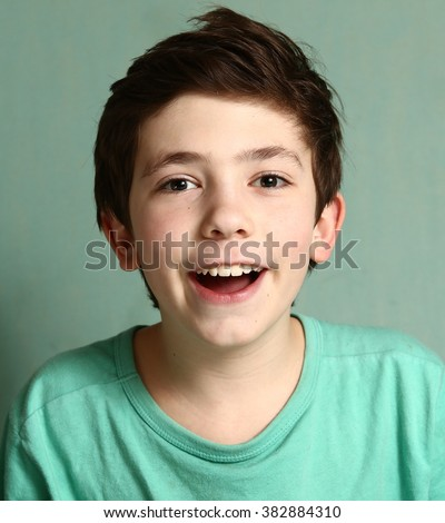 smiling laughing preteen boy with mouthful of healthy white teeth close up portrait in blue t-shirt - stock photo