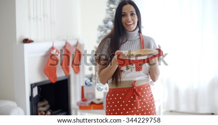 Smiling laughing young Christmas cook in a festive red apron holding a freshly baked tart in her hands in front of the Xmas tree