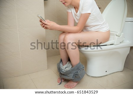 using the bathroom. smiling leisurely girl sitting on bathroom toilet in holiday morning and  using mobile smartphone chatting relaxing Smiling Leisurely Girl Sitting On Bathroom Stock Photo 651843529
