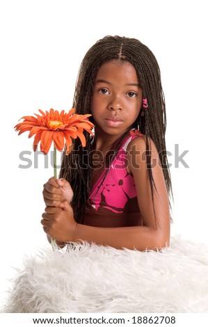 Smiling little African American girl with finger braids with her elbows on the bed holding a large orange flower