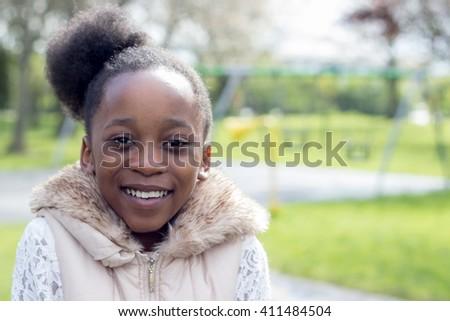 Smiling little African girl outside - stock photo
