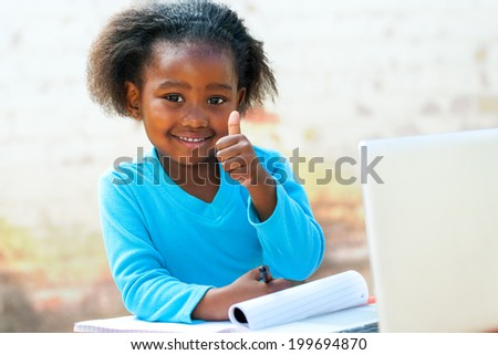 Smiling little African student doing thumbs up sigh at desk. - stock photo