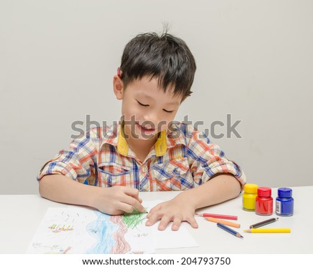 Smiling Little Asian Boy At The Table Draw With Color Pencils