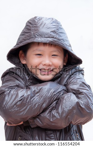 Smiling little asian boy in winter coat. - stock photo