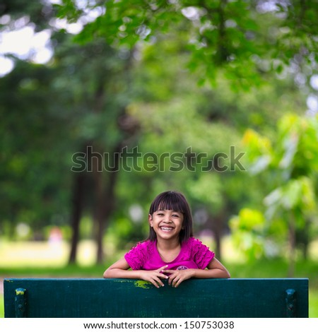 Smiling little asian girl sitting on the bench in park, Outdoor portrait - stock photo