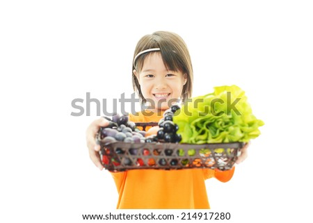 Smiling little Asian girl with vegetables - stock photo