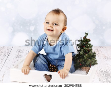 Smiling little baby boy with christmas tree - stock photo