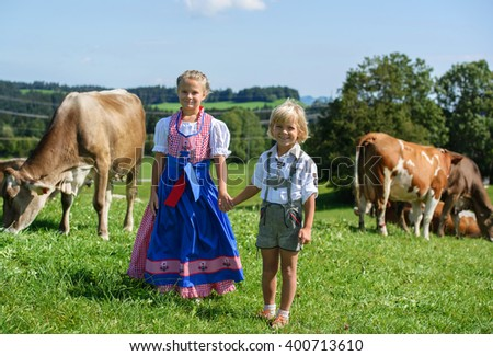 Smiling little bavarian boy with sister on a country field with cow in Germany - stock photo