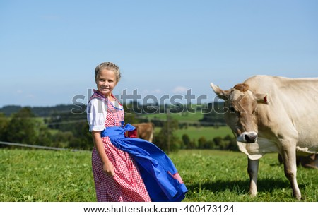 Smiling  little  bavarian girl on a country field  during Oktoberfest in Germany - stock photo