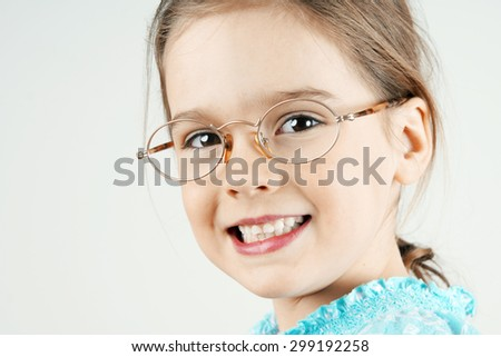 Smiling little blond girl with glasses - stock photo