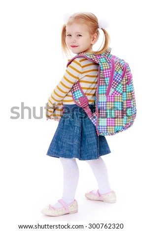 Smiling little blonde girl with long tails on the head are braided bows. The girl is dressed in a striped jumper and blue denim skirt with the back hanging on her school backpack . The girl turned - stock photo