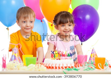 Smiling little boy and girl with birthday cake and color ballons