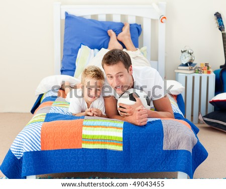 Smiling little boy and his father watching a football match in the kid's bedroom