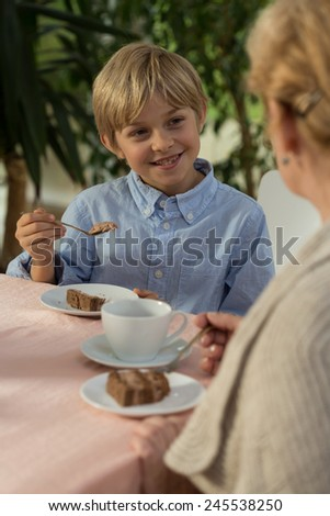 Smiling little boy and his granny during five o'clock tea - stock photo