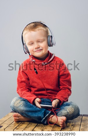 Smiling little boy closing his eyes while listening to music. Child in headphones enjoys music with smartphone in his hand  - stock photo