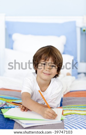 Smiling little boy drawing in bed with colorful pencils - stock photo