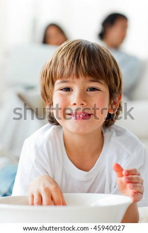 Smiling little boy eating chips lying on the floor in the living-room - stock photo