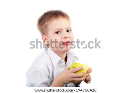 smiling little boy eating the big yellow apple - stock photo