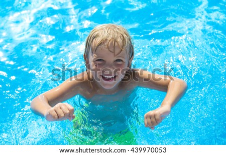 Smiling little boy has fun in swimming pool