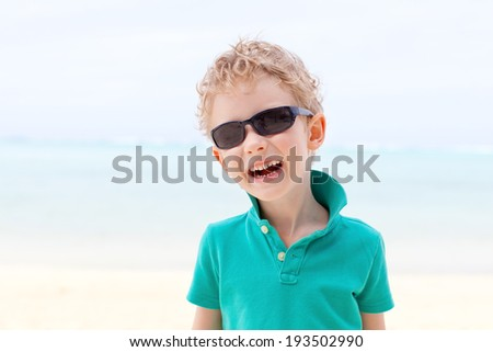 smiling little boy having fun at the beach during summer vacation
