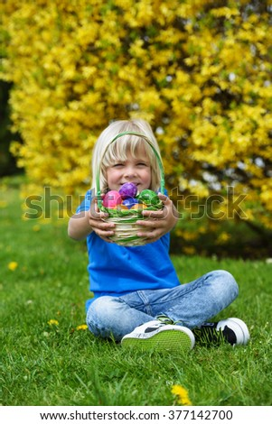 Smiling  little boy holding  basket full of colorful easter eggs outdoors on a sunny day  - stock photo
