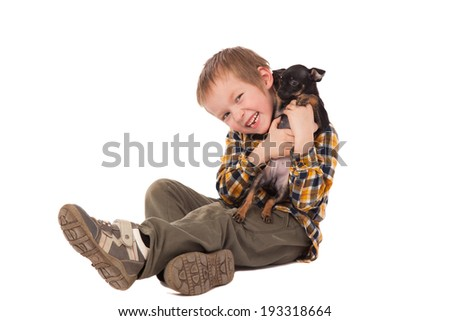 smiling little boy holding his puppy over white background - stock photo