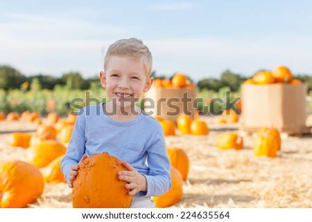 smiling little boy holding pumpkin while having fun at pumpkin patch at fall - stock photo