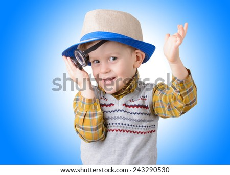 smiling little boy in a hat and glasses on blue background closeup - stock photo