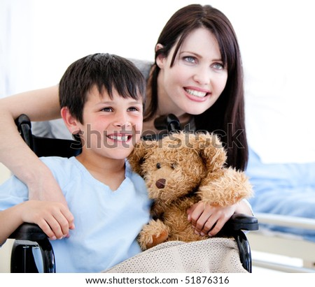 Smiling little boy in a wheelchair with his mother in a hospital - stock photo