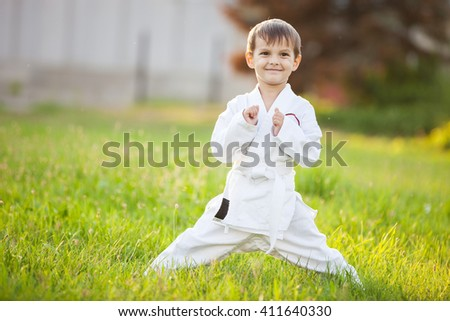 Smiling little boy in kimono standing on grass in park - stock photo