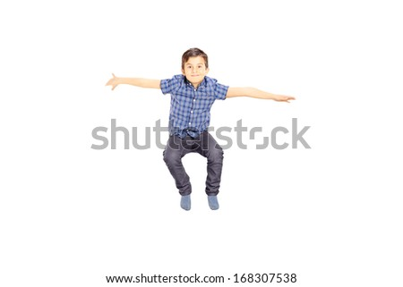 Smiling little boy jumping isolated on white background - stock photo