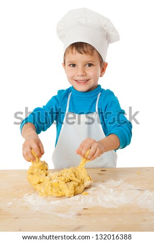 Smiling little boy kneading the dough on the table, isolated on white