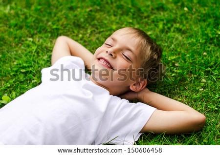 Smiling little boy lying in a field of green  - stock photo